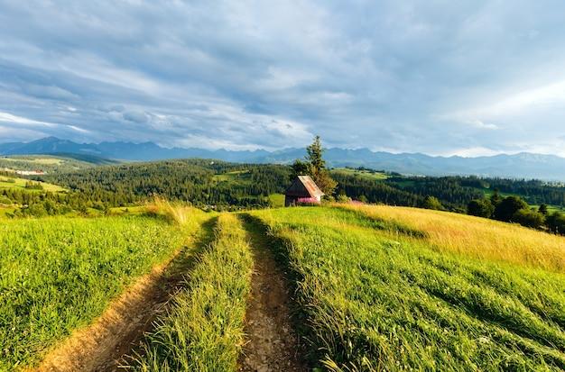 Sera d'estate periferia del villaggio di montagna con strada di campagna davanti e catena dei tatra dietro