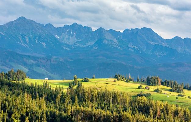 Serata estiva alla periferia del villaggio di montagna con la catena dei tatra dietro