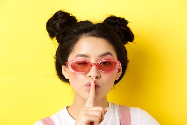 Concetto di moda estiva. ritratto del primo piano della donna asiatica glamour in occhiali da sole che racconta un segreto, chiede di stare zitto, fa il segno tabù del silenzio e ammiccante alla telecamera