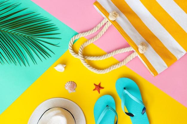 Estate piatta laici foglia di palma borsa da spiaggia cappello estivo infradito e conchiglie su un giallo rosa e turchese texture vacanza e concetto di moda vista dall'alto