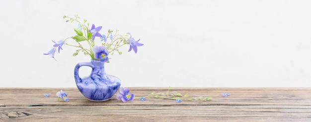 Fiori d'estate in brocca blu sul vecchio tavolo in legno