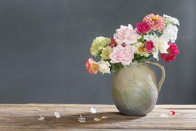Fiori estivi in brocca di ceramica su tavola di legno