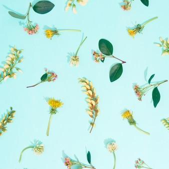 Reticolo di fiori estivi su sfondo blu. vista dall'alto, piatto.
