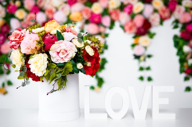 Fiori estivi in scatola rotonda e parola di legno amore su sfondo primaverile