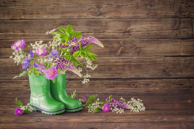Fiori estivi in stivali di gomma sul vecchio legno scuro