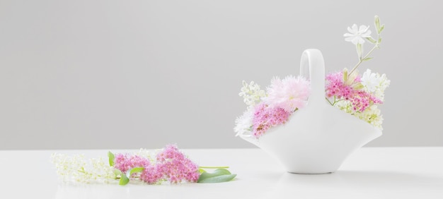 Fiori estivi in cesto in ceramica bianca