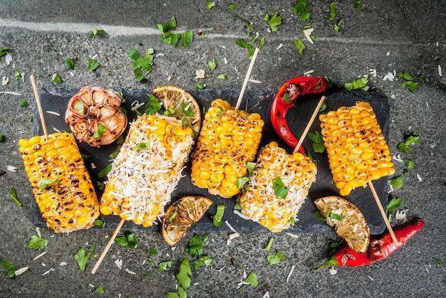 Cibo estivo. idee per grigliate e grigliate. mais alla griglia grigliato sul fuoco. con una spolverata di formaggio (elotes messicani), peperoncino e limone. su un tavolo di pietra scura. copia spazio vista dall'alto