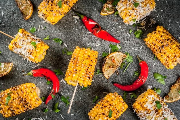 Cibo estivo. idee per grigliate e grigliate. mais alla griglia grigliato sul fuoco. con una spolverata di formaggio (elotes messicani), peperoncino e limone. su un tavolo di pietra scura. copia spazio