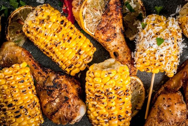 Cibo estivo. idee per barbecue, grigliate. mais e pollo (zampe, ali) grigliati, fritti a fuoco. con una spolverata di formaggio (elote), peperoncino piccante, limone. tavolo in pietra scura. chiudi vista dall'alto