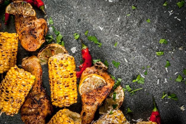 Cibo estivo. idee per barbecue, grigliate. mais e pollo (zampe, ali) grigliati, fritti a fuoco. con una spolverata di formaggio (elote), peperoncino piccante, limone. tavolo in pietra scura. copia spazio vista dall'alto
