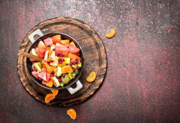 Cibo estivo insalata tropicale di frutta esotica su fondo rustico