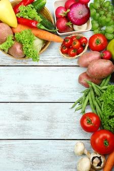 Cornice estiva con frutta e verdura biologica fresca su fondo in legno