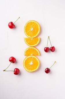 Ciliege della frutta di estate con le arance nella fila sulla vista bianca e superiore