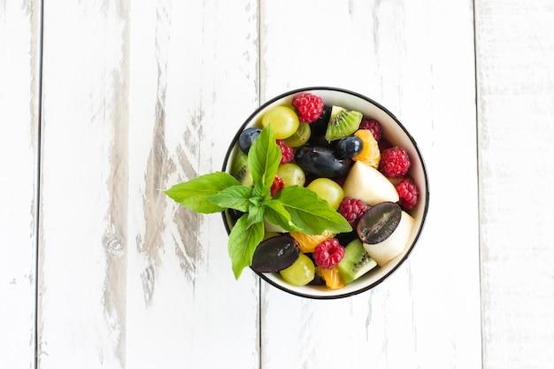 Macedonia di frutta estiva con foglie di menta in una ciotola su un tavolo di legno bianco. delizioso dessert, concetto di perdita di peso.
