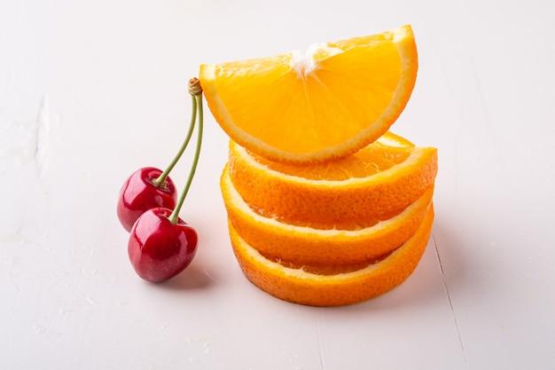 Ciliegie della frutta due di estate con le arance impilate su bianco