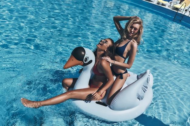 Divertimento estivo. due belle giovani donne in bikini che sorridono mentre galleggiano su un grande cigno gonfiabile