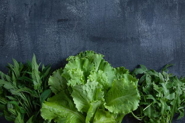 Verdi estivi su un tavolo scuro. manifesto dell'alimento di estate o concetto dell'insegna. vista dall'alto. copia spazio per il design. concetto di eco, verde, alimenti biologici