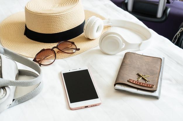 Estate cappello occhiali da sole borsa cuffia passaporto e smartphone del viaggiatore donna sul letto nella moderna camera d'albergo viaggi relax viaggio viaggio e concetti di vacanza close up e copia spazio