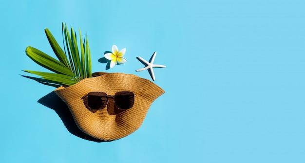 Cappello estivo con occhiali da sole su sfondo blu. goditi il concetto di vacanza.