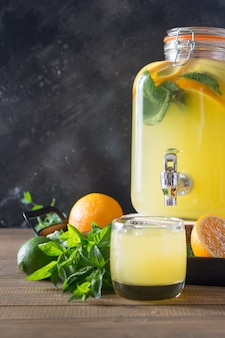 Bevanda disintossicante salutare estiva. limonata con arancia, limone e menta in barattolo di vetro su tavola di legno.