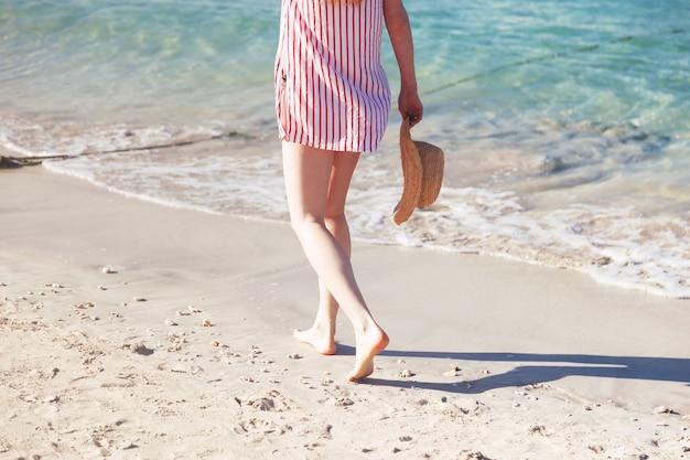 Concetto di moda per le vacanze estive - donna che cammina lungo la riva del mare con il cappello in mano