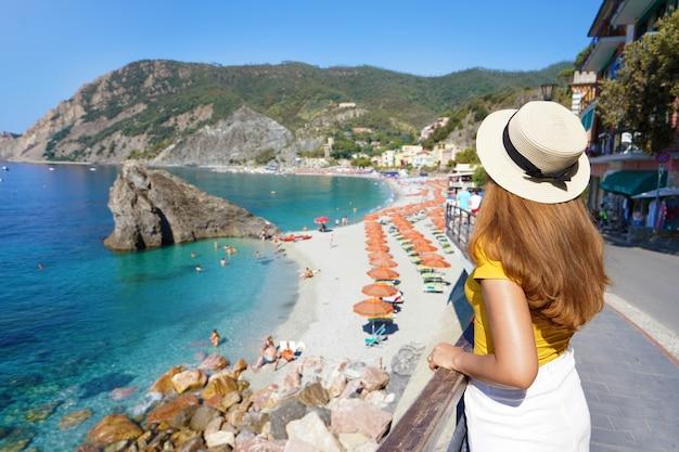 Vacanze estive in italia. vista posteriore della giovane donna con cappello nel villaggio di monterosso al mare, cinque terre, italia.