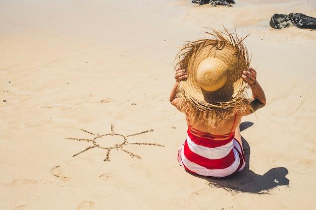 Vacanze estive vacanze in spiaggia in paradiso bellissimo resort persone concetto con bella donna con cappello turistico visto dal retro godendosi la sabbia e con il sole disegnato sul suo lato