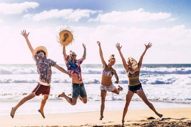 Concetto di viaggio per le vacanze estive con un giovane gruppo di amici che saltano per la felicità e la gioia in spiaggia con mare blu e cielo che si godono la natura e il tempo libero all'aperto activ