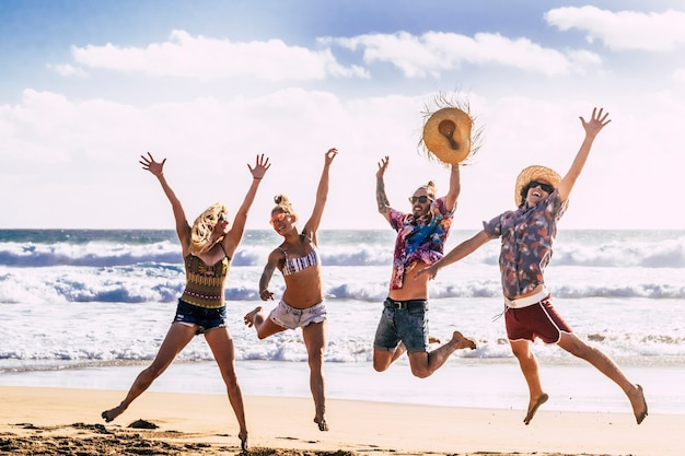 Concetto di viaggio per le vacanze estive con un giovane gruppo di amici che saltano per la felicità
