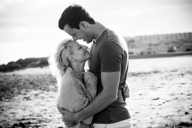 Vacanze estive, amore, romanticismo e concetto di persone - giovane e bella coppia sorridente felice che si abbraccia all'aperto - vacanza romantica in bianco e nero sulla spiaggia per felice giovane millenario uomo e donna