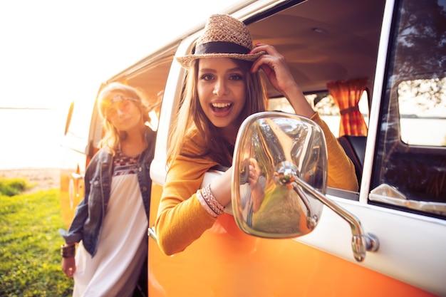 Vacanze estive, viaggio su strada, vacanze, viaggi e concetto di persone - amici hipster in viaggio su strada in una giornata d'estate
