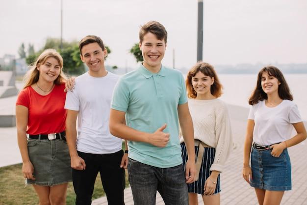 Vacanze estive e concetto adolescente - gruppo di adolescenti sorridenti che vanno in giro fuori.