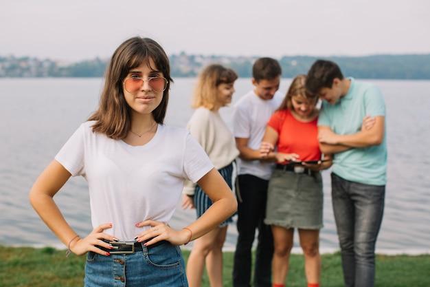 Vacanze estive e concetto adolescente - gruppo di adolescenti sorridenti con tablet appeso fuori.