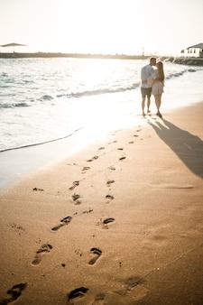 Vacanze estive e viaggi. donna e uomo sexy in acqua di mare al tramonto. le coppie amorose si rilassano sulla spiaggia dell'alba. relazione d'amore di una coppia che si gode una giornata estiva insieme. messa a fuoco selettiva