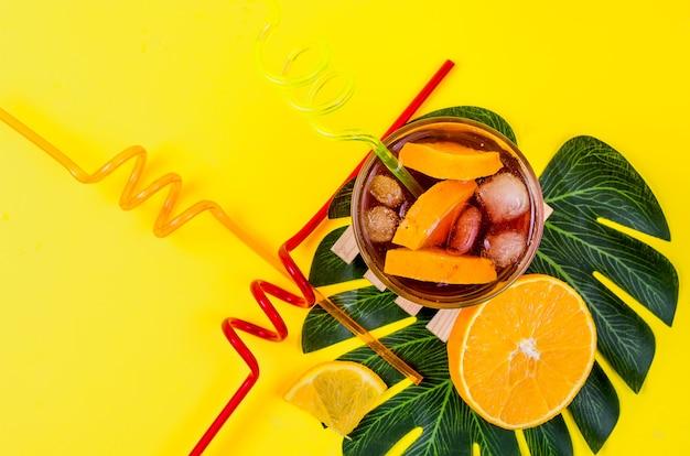 Cocktail di sangria rosso freddo casalingo di estate con arancia e ghiaccio in vetro su colore giallo