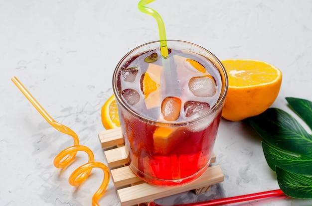 Cocktail di sangria rosso freddo fatto in casa estivo con arancia e ghiaccio in vetro
