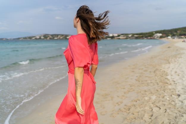 Immagine di estate di donna sexy felice in splendido abito rosa in posa sulla spiaggia.