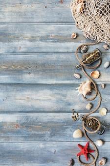 Decorazione interna estiva con stelle marine, conchiglie, corde e bottiglie con pietre su fondo di legno blu. copia spazio. natura morta. lay piatto