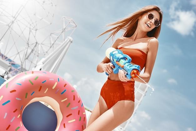 Asciugamani estivi isbikini che si crogiolano al sole delle spiagge degli oceani solo per divertirsi a sparare a una giovane donna