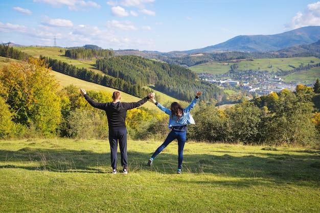 Paesaggio estivo in montagna e un bel cielo azzurro con nuvole: una coppia amorevole seduta sullo sfondo