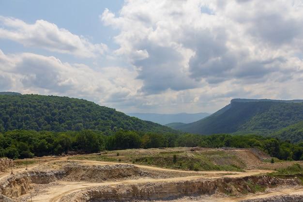 Paesaggio estivo con cava di calcare contro montagne e cielo nuvoloso