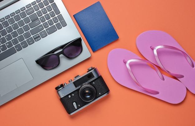 Tempo libero estivo. relax estivo. accessori per laptop e spiaggia su sfondo corallo. studio breve. oggetto spiaggia.