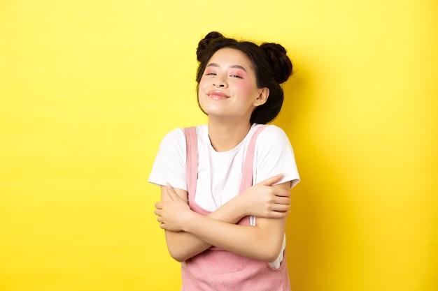 Concetto di stile di vita estivo. bella donna asiatica che si abbraccia e che sorride romantica, abbracciando il proprio corpo, in piedi con il trucco sul giallo.