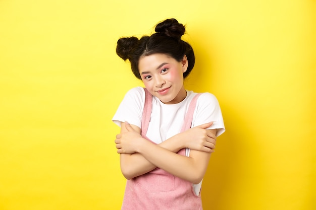 Concetto di stile di vita estivo. ragazza asiatica carina di bellezza con il trucco, abbracciarsi e sorridente romantico, tenero in piedi sul giallo.
