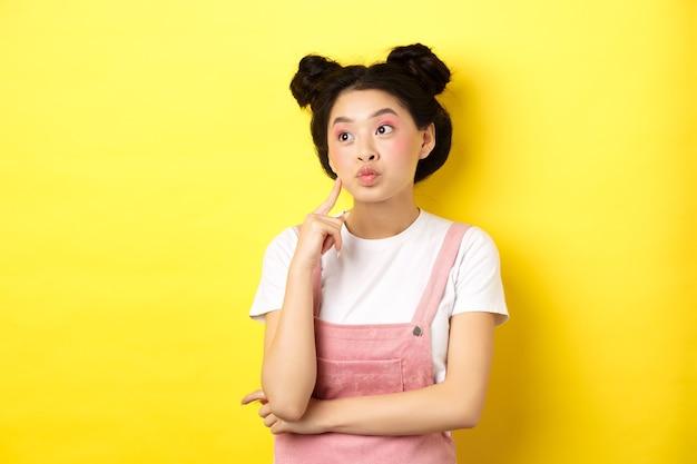 Concetto di stile di vita estivo. ragazza asiatica pensierosa glamour pensando, guardando a sinistra il logo e sognando, facendo una scelta, in piedi sul giallo