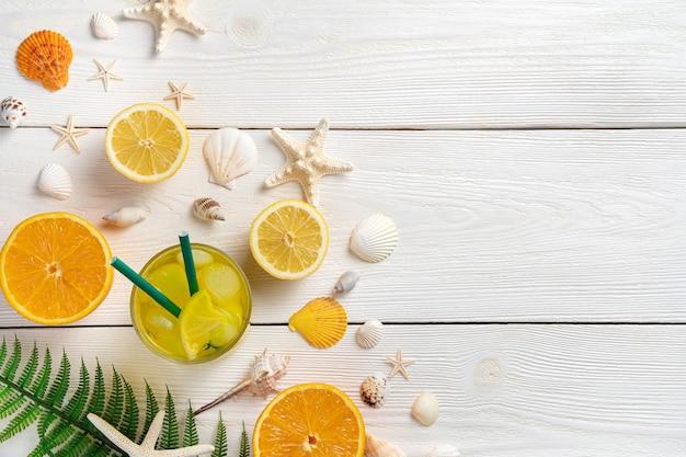 Fondo di legno chiaro di estate con frutta e una bevanda rinfrescante.