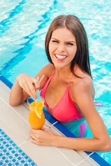 L'estate mi fa impazzire! giocosa giovane donna in bikini che tiene in mano un cocktail e mostra la lingua mentre sta in piedi in piscina