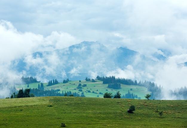 Estate nebbiosa periferia del villaggio di montagna con la catena dei tatra