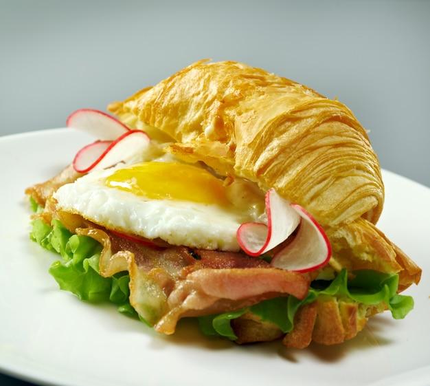 Summer morning breakfast croissant ripieno di uova strapazzate e pancetta fritta