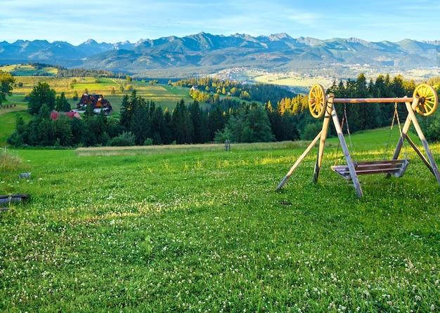 Mattina d'estate vista nebbiosa del villaggio di montagna e altalena davanti alla catena dei tatra dietro,